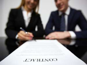 woman in distance signing a long contract