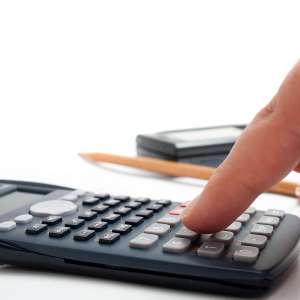finger adding up figures using a calculator