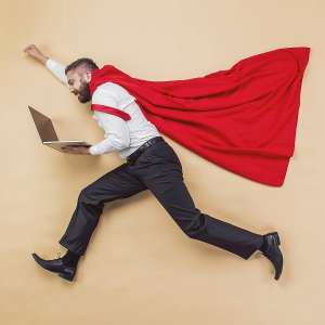male officer worker with laptop and red cape leaping like superman