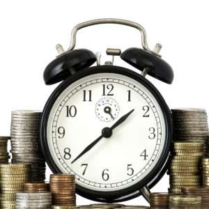 alarm clock with coins: time is money concept
