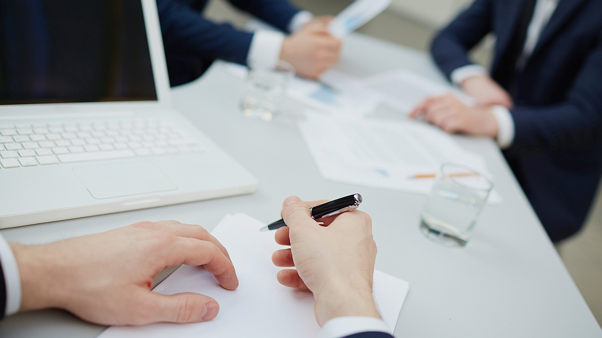 man's hands in meeting ready to take notes