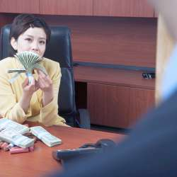 business woman counting money in office