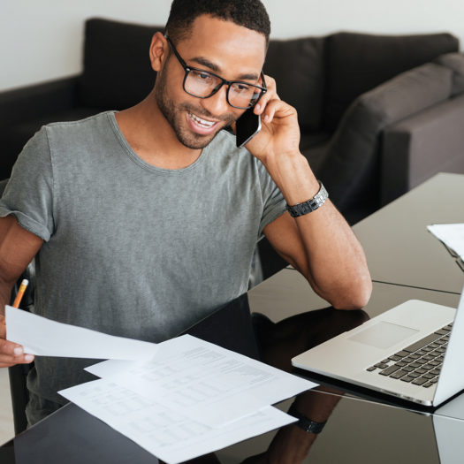 Man talking on mobile phone while looking at accounting documents